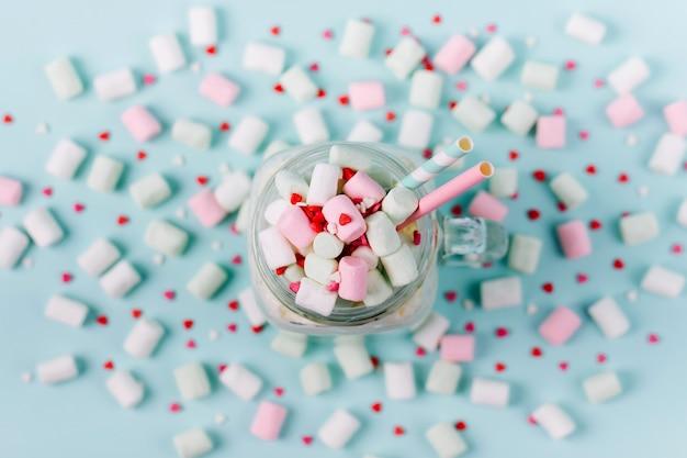 Frappè con marshmallows in un barattolo di vetro su sfondo blu