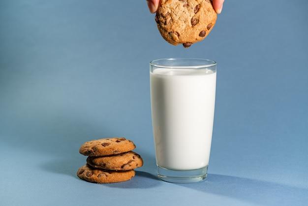 Latte con spruzzata e biscotti al gusto di cioccolato su sfondo blu.