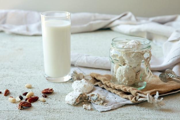 Latte con gustosi biscotti alle noci fatti in casa con arachidi su sfondo di cemento
