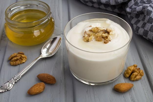 Yogurt al latte con miele e noci sulla superficie di legno grigia