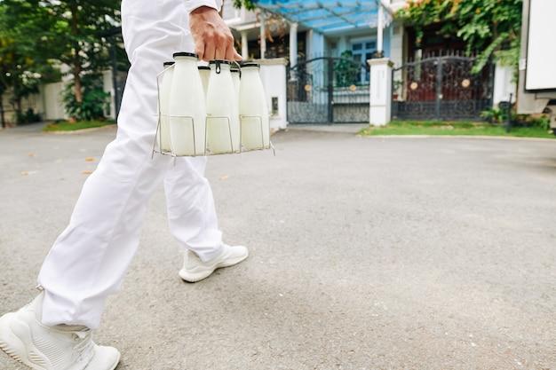 Lattaio in uniforme bianca che trasportano bottiglie di vetro alle porte d'ingresso del cliente