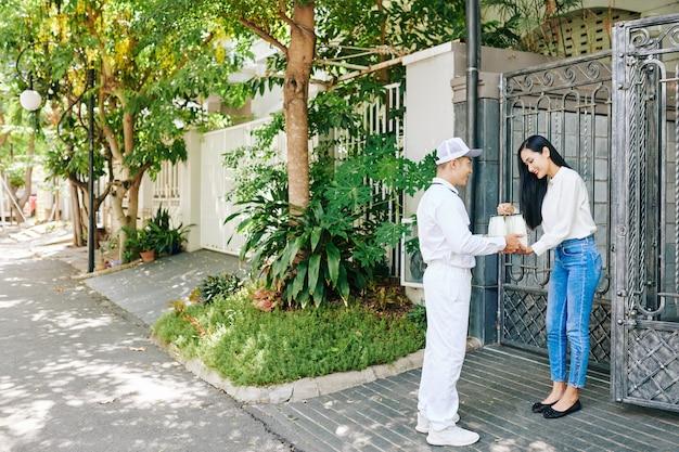 Lattaio in uniforme bianca che dà set di latte in bottiglia di vetro alla bella giovane donna asiatica