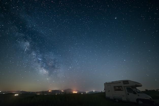 La via lattea e le stelle sopra un camper parcheggiato.