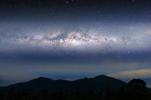 Luce del paesaggio notturno della via lattea sopra la montagna della siluetta, lo spazio e le stelle sullo sfondo del cielo