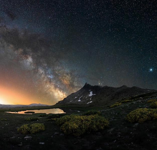 Via lattea su un paesaggio notturno nelle montagne della spagna