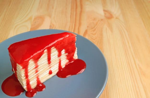 Mille crepe cake con salsa di lamponi sul piatto blu servito sul tavolo di legno