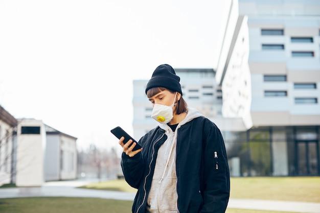 Millenial girl in black minimal clothes utilizza lo smartphone con maschera respiratoria sul viso, giovane donna in abbigliamento casual in piedi sulla strada con telefono e maschera di protezione