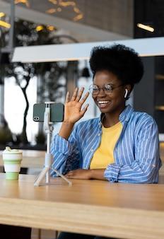 Donna millenaria afroamericana in un luogo pubblico che guarda un webinar o chatta su una webcam da