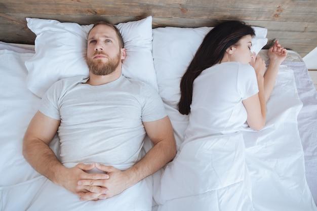 Uomo barbuto millenario sdraiato a letto e pensando a qualcosa mentre sua moglie dorme vicino a lui