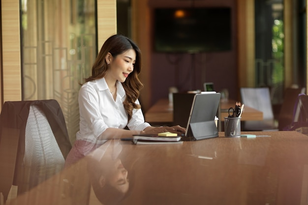 La millenaria donna d'affari negozia il prodotto di importazione aziendale con il fornitore tramite tablet digitale