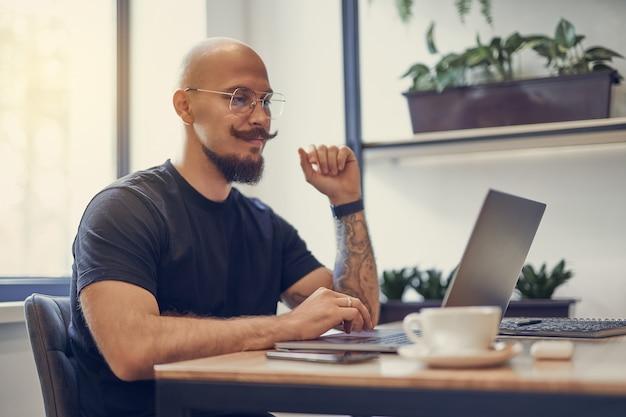 L'uomo caucasico millenario lavora al computer a casa lavoro a distanza