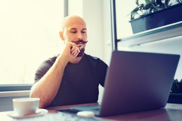 L'uomo caucasico millenario lavora al computer in ufficio a casa tiene una penna in mano lavoro a distanza