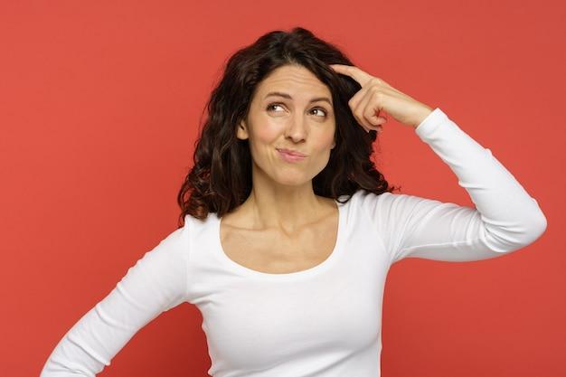 La mentalità femminile millenaria pensa al piano di soluzione o all'idea con un sorriso astuto cerca isolato su rosso