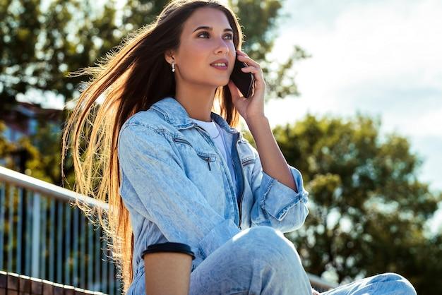 La ragazza millenaria in vestiti di jeans si siede su una panchina nel parco, comunica con amici, colleghi, genitori al telefono.