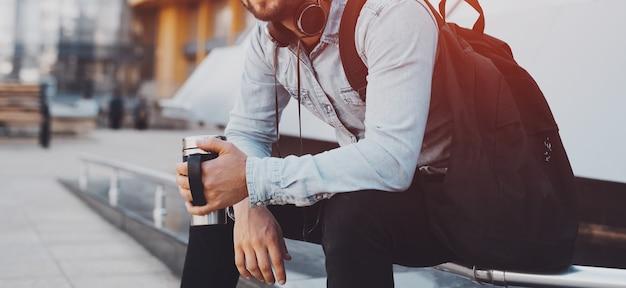 Ragazzo millenario con zaino, che indossa le cuffie al collo, che tiene la tazza termica del caffè nelle mani.
