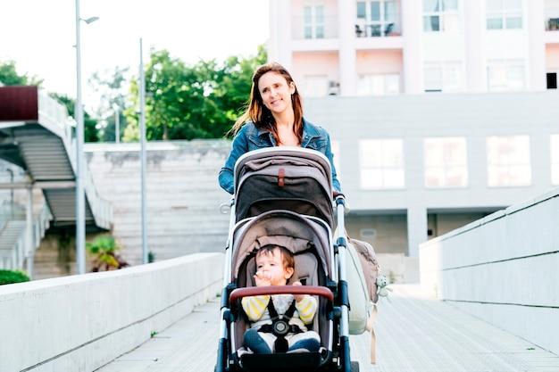 Mamma millenaria che porta i suoi bambini a fare un passeggino estivo in città