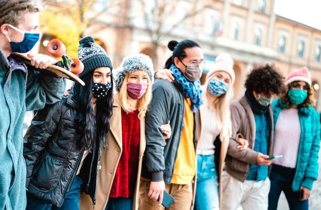 Gruppo di persone millenarie che camminano e si divertono insieme indossando una maschera per il viso al centro della città