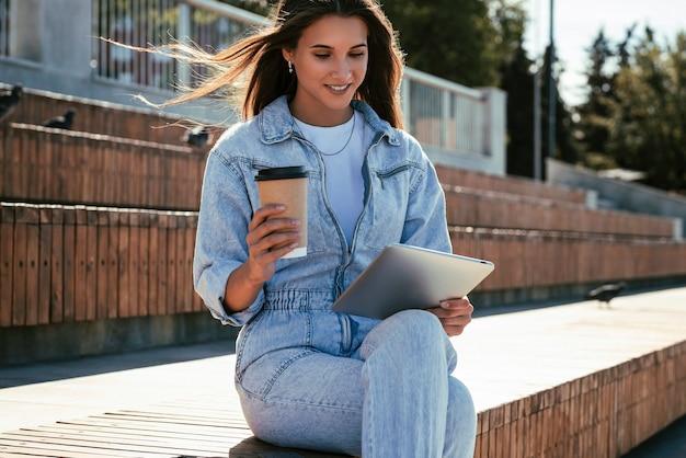 La donna millenaria in vestiti di jeans si siede su una panchina nel parco, con in mano un tablet intelligente. la donna usa la compressa