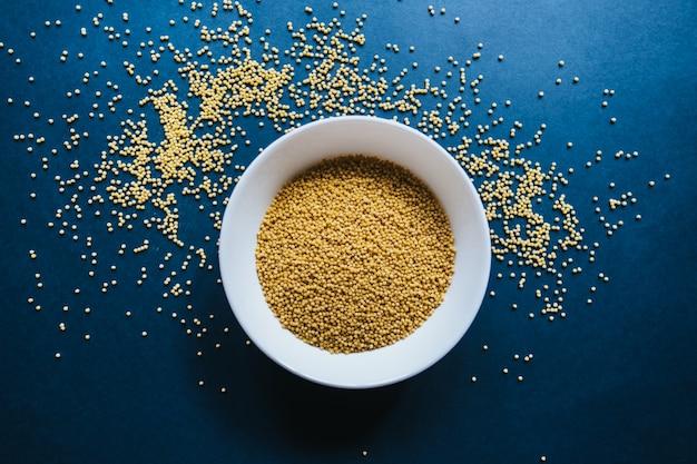 Porridge di miglio in un piatto bianco su sfondo blu.