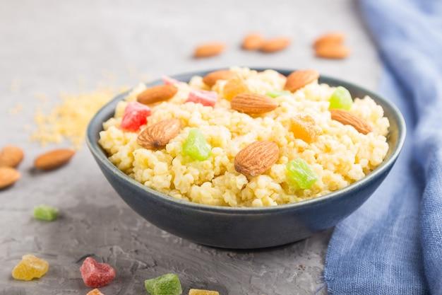 Porridge di miglio con frutta candita e mandorle in ciotola di ceramica blu su un cemento grigio.