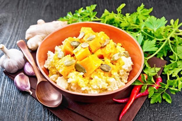 Porridge di miglio con salsa di zucca piccante e semi in una ciotola di argilla su legno