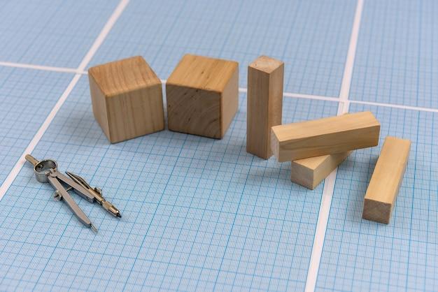 Carta millimetrata con strumenti di disegno e blocchi di legno
