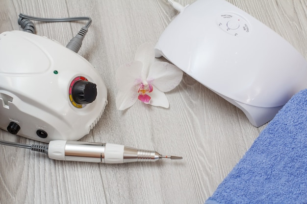 Fresa, lampada uv a led e asciugamano blu con fiore di orchidea bianca su fondo di legno grigio. un set di strumenti cosmetici per la manicure hardware professionale. vista dall'alto