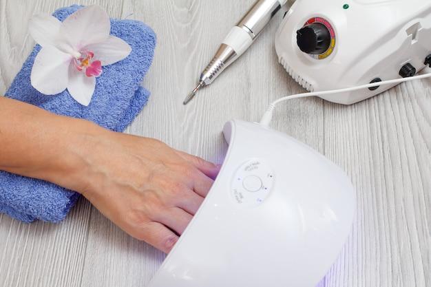 Fresa e lampada uv a led che asciugano le unghie della donna su fondo di legno grigio. un set di strumenti cosmetici per la manicure hardware professionale. vista dall'alto.
