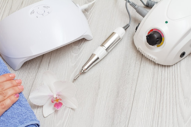 Fresa, lampada uv a led e una mano femminile su un asciugamano su fondo di legno grigio. un set di strumenti cosmetici per la manicure hardware professionale. vista dall'alto