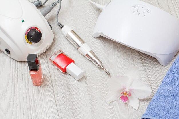 Fresa, lampada uv a led, smalti per unghie e asciugamano su fondo di legno grigio. un set di strumenti cosmetici per la manicure hardware professionale. vista dall'alto.