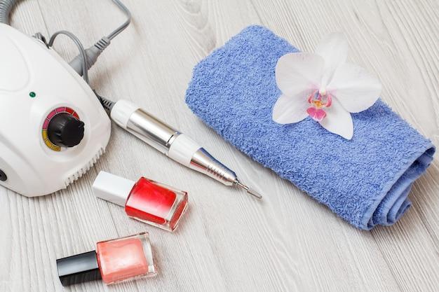 Fresa, smalti per unghie e asciugamano su fondo di legno grigio. un set di strumenti cosmetici per la manicure hardware professionale. vista dall'alto.