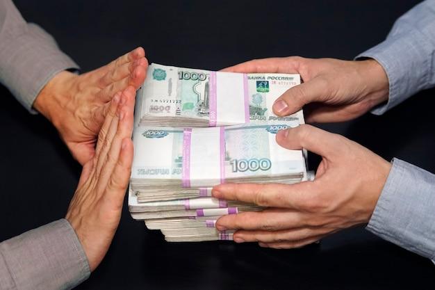 Un milione di rubli nelle mani degli uomini. corruzione in rubli russi in una stanza buia. il concetto di corruzione e concussione. il rifiuto del denaro. l'onesto funzionario rifiuta una tangente.