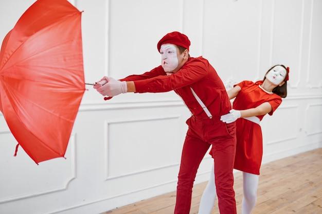Artisti di mimo, scena con l'ombrello in tempo ventoso
