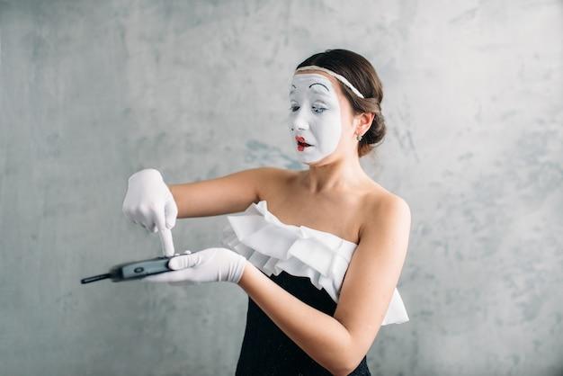 Artista femminile del mimo che esegue con il telefono cellulare. pagliaccio del circo della donna.