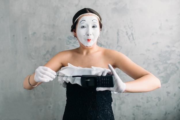 Artista femminile del mimo che esegue con il telefono cellulare