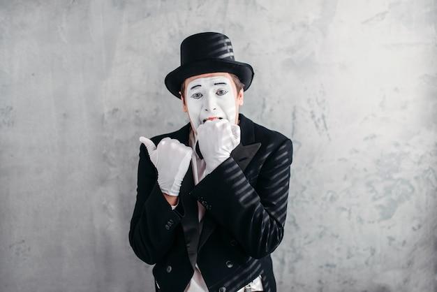 Mimica persona di sesso maschile con maschera bianca per il trucco.