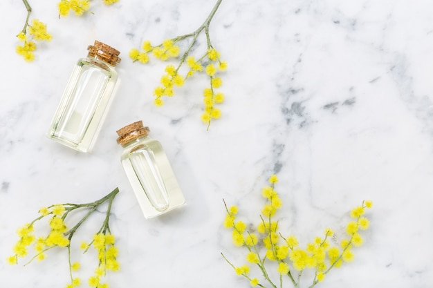 Olio essenziale di mimosa su tavolo di marmo. olio di dealbata di acacia