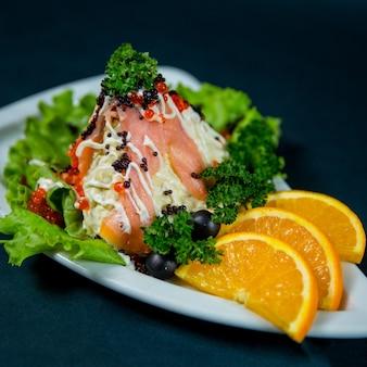 Insalata di mimosa decorata con erbe e fette d'arancia in un piatto da vicino su sfondo scuro
