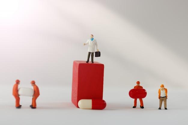 Persone in miniatura: dottore in piedi su un blocco rosso con capsula.