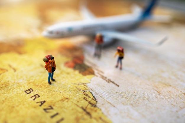 Persone in miniatura: viaggiare con uno zaino in piedi sulla mappa del mondo vintage, viaggi e concetto estivo. Foto Premium
