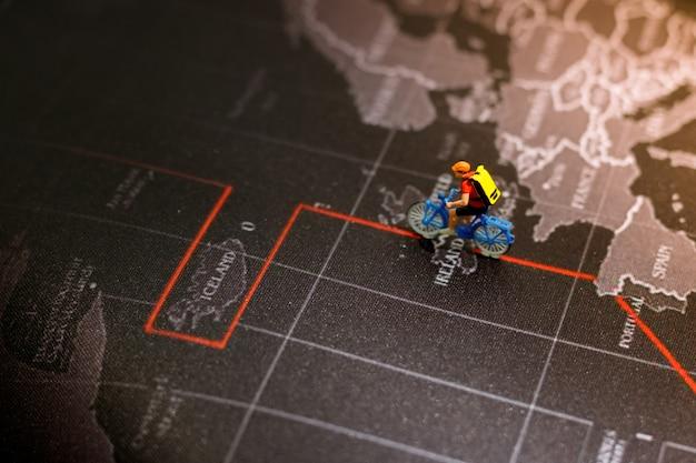Persone in miniatura: viaggiare con uno zaino che viaggiano in bicicletta.