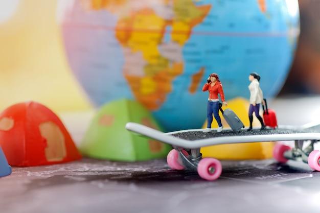 Persone in miniatura: viaggiare con una borsa e una mappa del mondo.