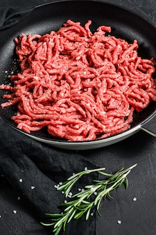 Tritare. carne macinata con ingredienti per cucinare. sfondo nero. vista dall'alto