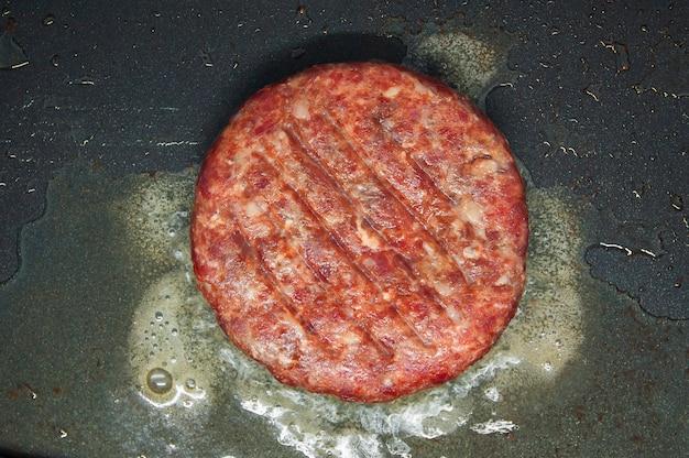 Carne macinata o hamburger cotti in padella. vista dall'alto.