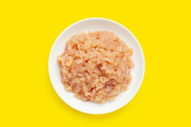 Carne macinata di filetto di pollo in piastra bianca su sfondo giallo.