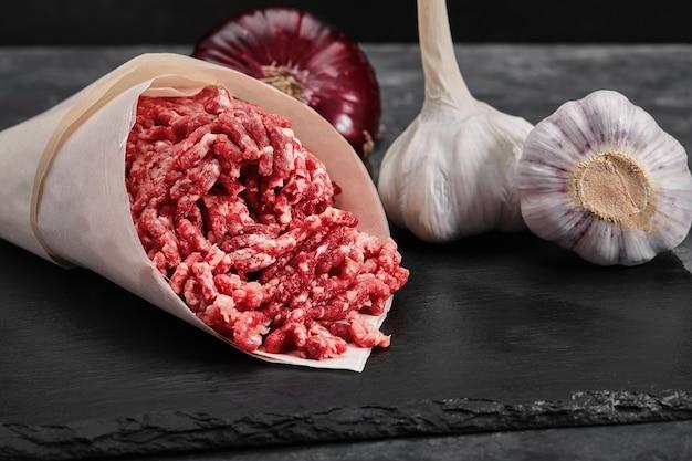 Carne macinata su carta con condimento e aglio fresco su sfondo nero, vista laterale.