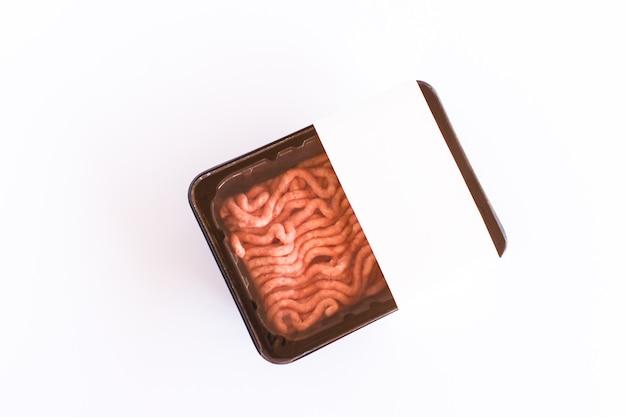 Carne di maiale macinata in imballaggi di plastica sottovuoto su sfondo bianco. vista dall'alto. progettazione del layout del logo.