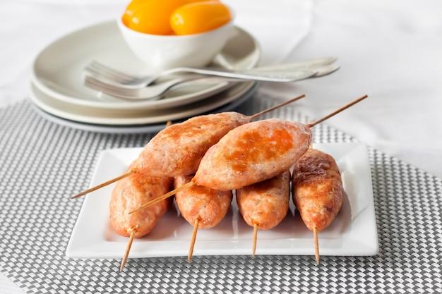 Spiedini di tacchino tritato su piatto quadrato e pomodori marinati gialli in background