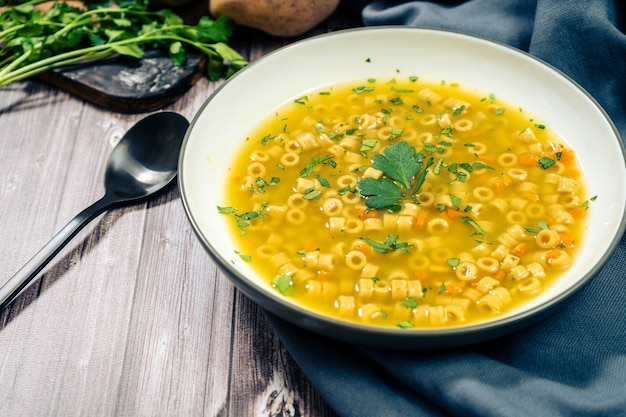 Vista macinata di una squisita zuppa di pollo e verdure con tagliatelle e prezzemolo