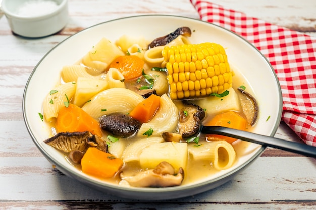 Vista macinata di una squisita zuppa di pollo, verdure e funghi fatta in casa con noodles e mais. concetto di cibo naturale e sano